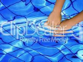 Hände tauchen in ein Schwimmbecken mit Verzerrung an der Wasseroberfläche