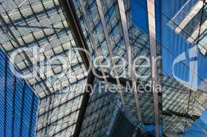Glasfassade mit Spiegelung eines modernen Bürokomplexes
