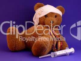 Kranker Teddy mit Verband und Spritze