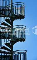 Wendeltreppe am der Außenfassade eines Hause mit blauen Himmel im Hintergrund