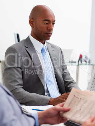 Businessman reading a newspaper with his colleague workig at a c