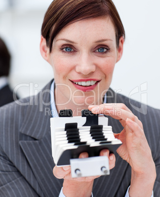 Portrait of a young businesswoman consulting her business card h
