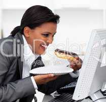 Close-up of a laughing businesswoman eating a chocolate eclair