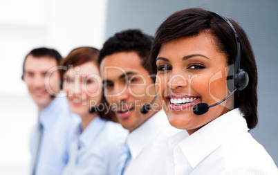Ethnic businesswoman with headset on smiling at the camera