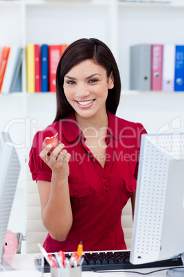 Young businesswoman eating a fruit