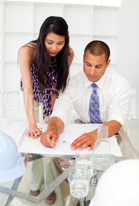 Two architects discussing a construction plan in the office