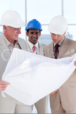 Three engineer co-workers studying plans