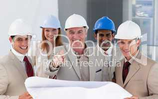 A group of smiling architects studying blueprints