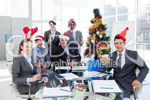 Portrait of a smiling business team wearing novelty Christmas ha