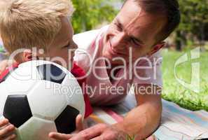 Close-up of an attentive father and his son holding a soccer bal