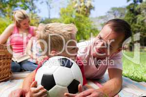 Father and son holding a soccer ball with their family reading i