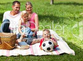 Happy parents and children picnicing in the park