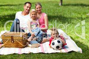 Parents and children relaxing at a picnic