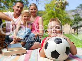 Little boy having fun with a soccer ball with his family smiling