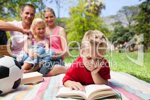 Concentrated blond boy reading while having a picnic with his fa