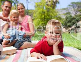 Smiling little boy reading lying on the grass while having a pic