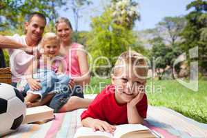 Little boy reading lying on a picnic tablecloth