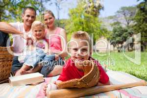 Smiling little boy wearing a baseball glove while having a picni