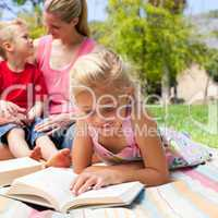 Concentrated blond girl reading while having a picnic with her f