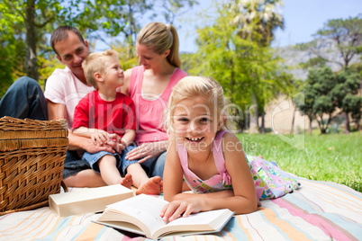 Blond girl reading lying on a picnic tablecloth
