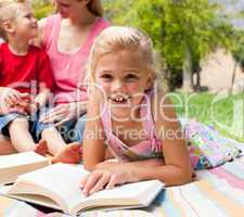 Close-up of a little girl reading at a picnic
