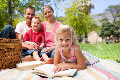 Cute little girl reading lying on the grass while having a picni