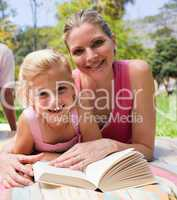 Happy mother and her daughter reading in a park