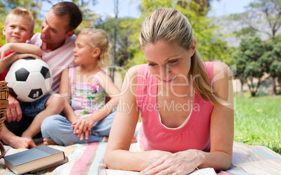 Concentrated mother reading at a picnic with her family