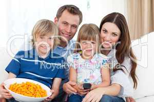 Portrait of a smiling family eating crisps while watching TV