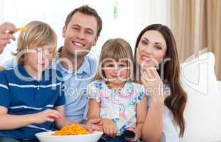 Happy family eating crisps