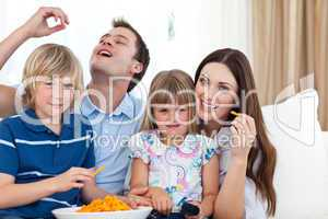 Young family eating crisps while watching TV
