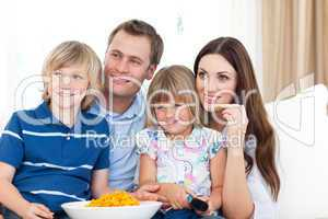 Family watching television and eating chips