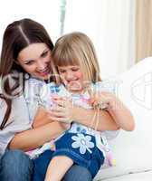 Cute girl sitting on her mother's lap celebrating a goal