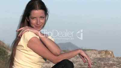 HD young woman sitting on top of the mountain