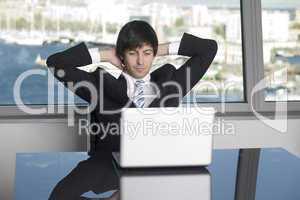 Zufriedener Geschäftsmann lehnt sich zurück vor seinem Computer nach einem guten Verkauf