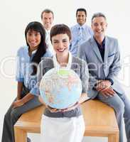 Cheerful multi-ethnic business people holding a terrestrial glob
