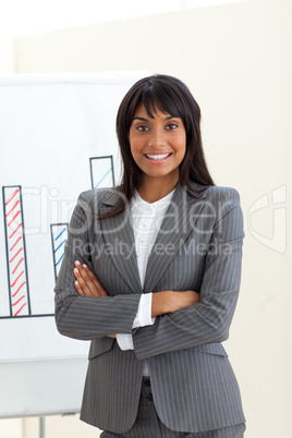 Ethnic businesswoman with folded arms in front of a board