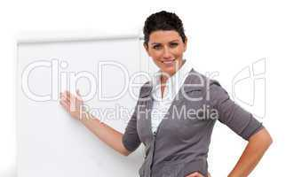 Confident female executive pointing at a board