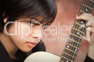 Attractive Ethnic Girl Plays Guitar