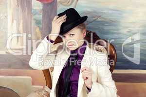 Beautiful young blond woman in black hat.