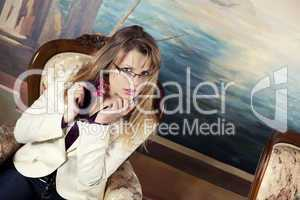 Sexy blond girl with glasses sitting on a luxury armchair