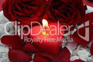 Herzkerze mit Rosen auf Granitsteinen