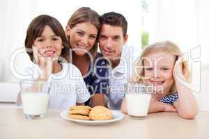 Children eating biscuits and dinking milk with their parents