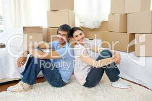 Happy couple relaxing while moving house