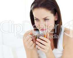 Delighted woman drinking a tea