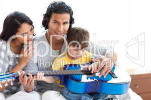Cute little boy playing guitar with his parents