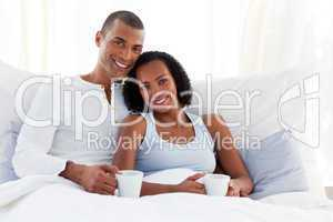 Afro-american couple drinking a coffee on their bed