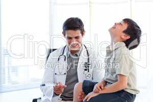 Smiling doctor checking a child's reflex