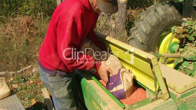Farmer Filling Seeder With Wheat