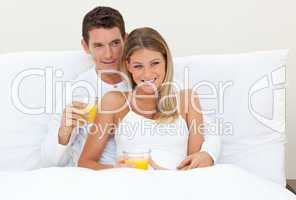 Affectionate couple drinking orange juice lying on their bed